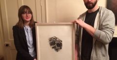 UCS BA (Hons) Fine Art students, Emily Godden and Adam Riches holding the Maggi Hambling work of art donated by the artist for their fundraising auction