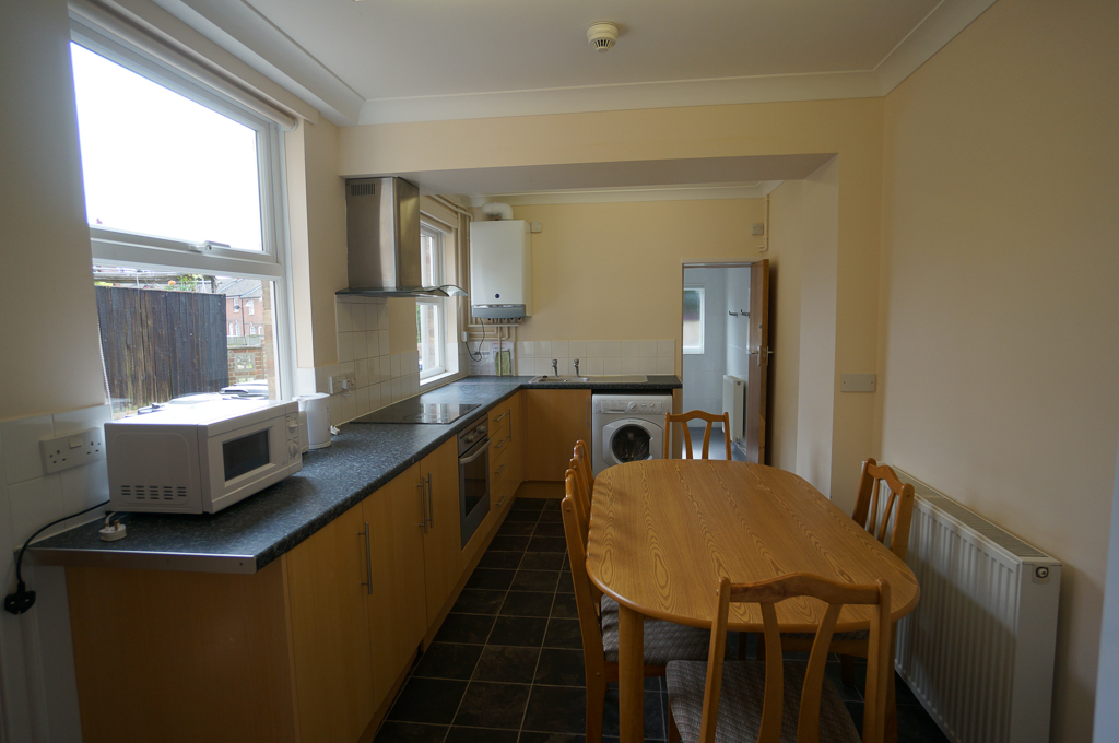 Kitchen with microwave, oven, hob, washing machine, dining table and chairs