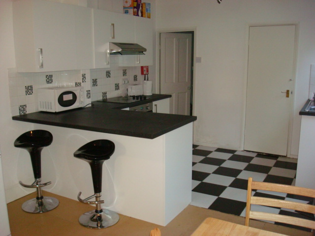 Kitchen with microwave, oven, hob, breakfast bar and stools