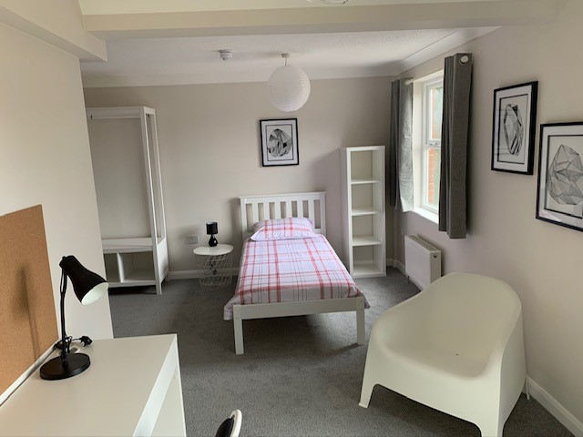 Bedroom furnished with bed, wardrobe, shelving chair and desk