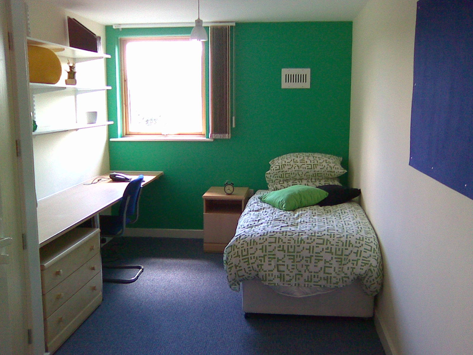 A study bedroom showing a bed, bedside cabinet, desk and chair
