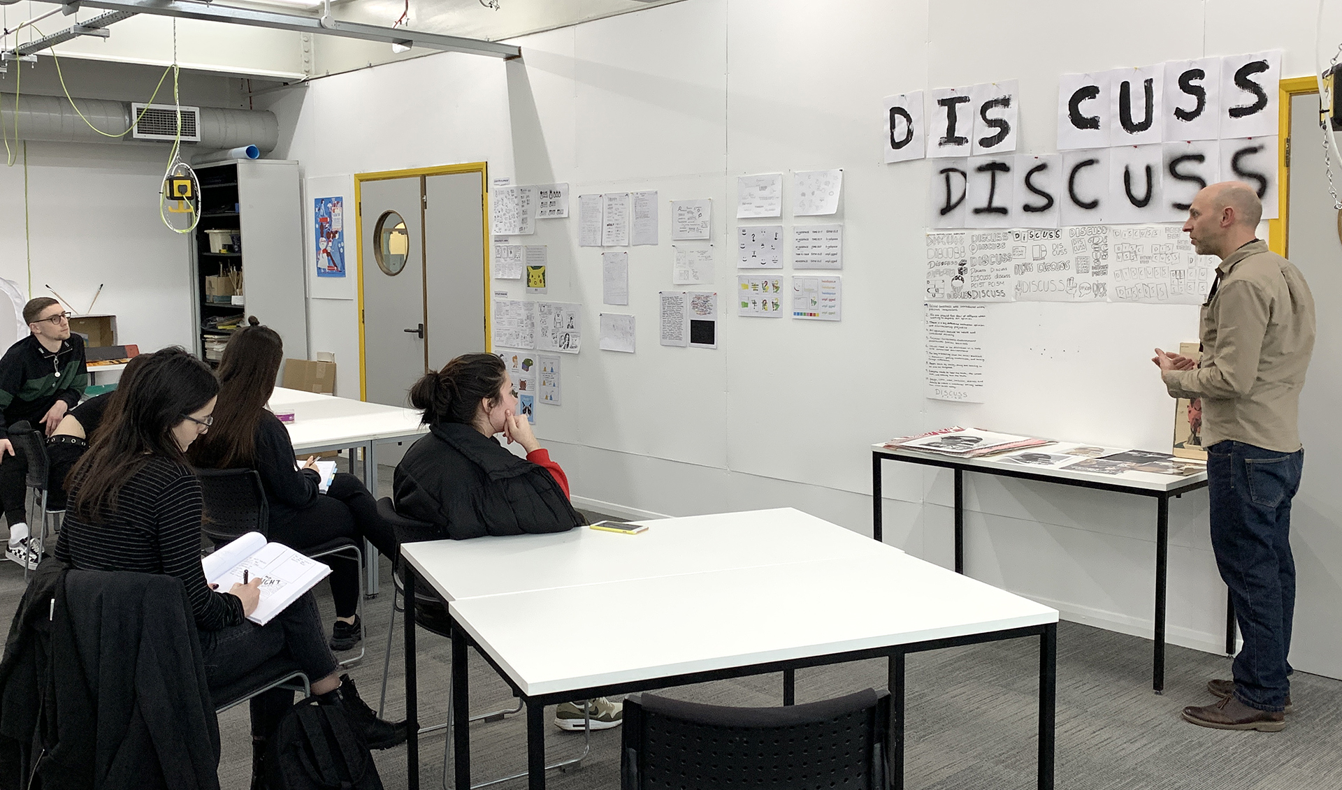 A photograph of students involved in a critique of work pinned on the wall