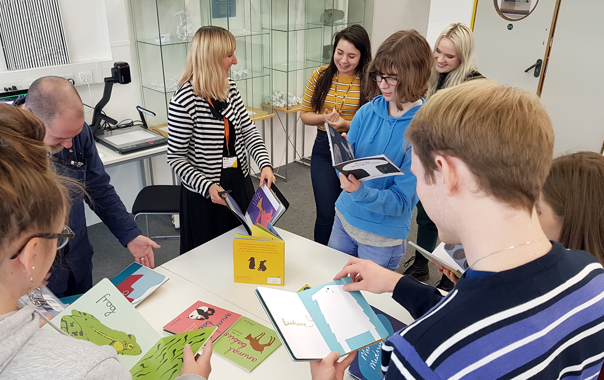A photograph of students standing around a table looking at children's picture books and talking to an illustrator