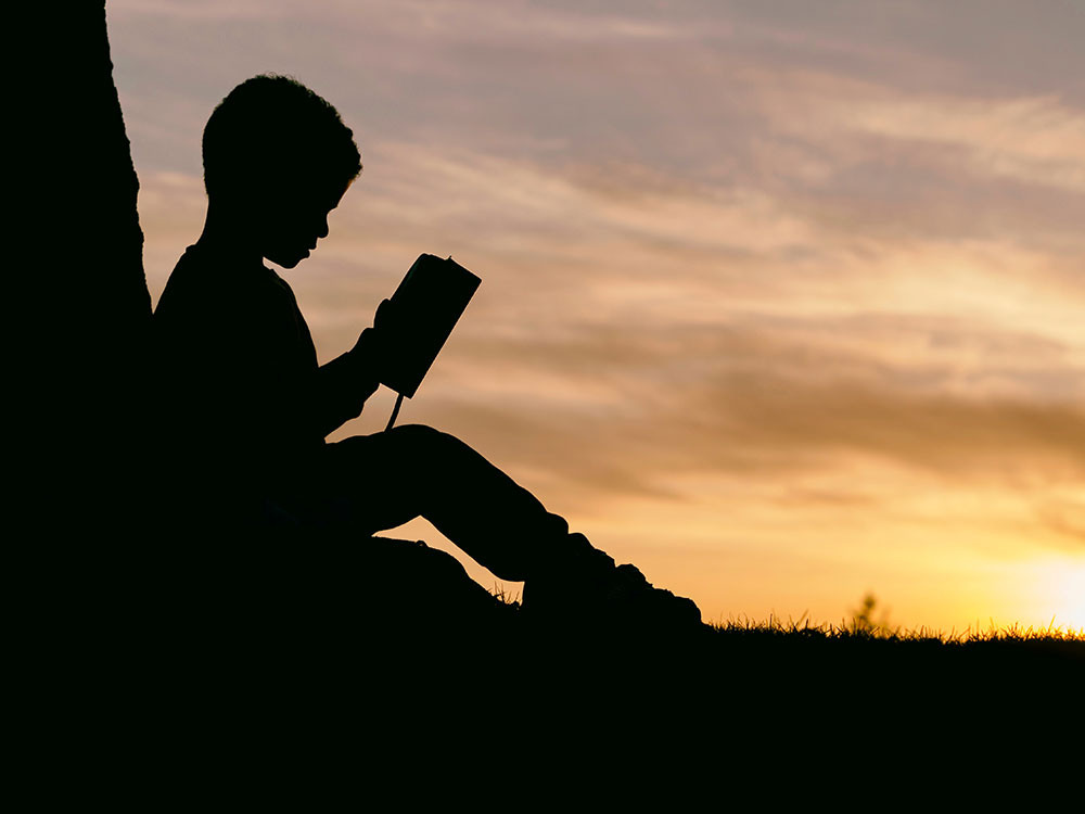 Silhouetted child reading