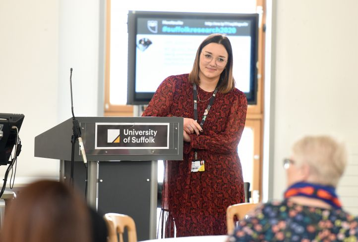 Female Research Associate giving speech at conference